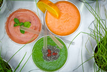 reciclable: Strawberry, raspberry, orange, kiwi and avocado smoothies in plastic recyclable cups