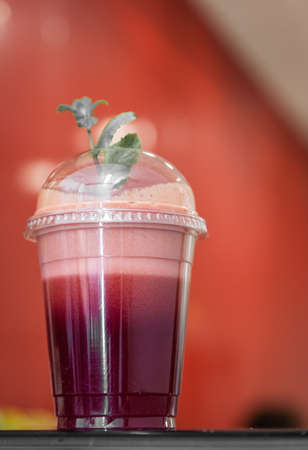 reciclable: Fresa y frambuesa batido en un vaso de pl�stico reciclable con una paja