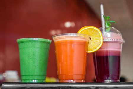 reciclable: Fresa, frambuesa, naranja, kiwi y aguacate batidos en vasos de plástico reciclables