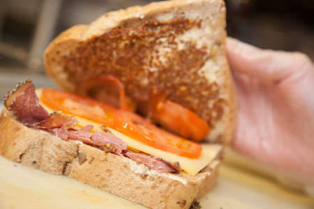 wholegrain mustard: Close up of a person hands showing ham, cheese and tomato sandwich in a cafeteria