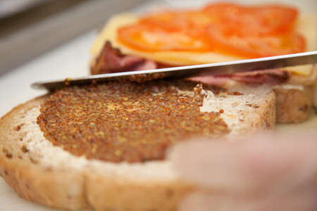 wholegrain mustard: Close up of a person hands spreading wholegrain mustard on a ham, cheese and tomato sandwich in a cafeteria Stock Photo