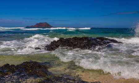 lobos: Waves hitting the shore  in Corralejo Dunes National Park in Fuerteventura, Canary Island, Spain with Los Lobos Island in the background Stock Photo