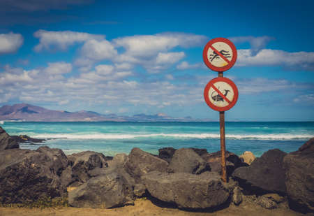 no swimming sign: No swimming, no fishing signs on the coast in Corralejo, Fuerteventura, Canary Islands, Spain Stock Photo