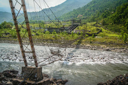 rapid steel: Damaged bridge over the Bhote khosi river, flowing through the beautiful mountain valley in the mountains of Nepal Stock Photo