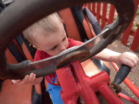 immobile: Little boy sitting behind the wheel of an immobile car truck in a playground