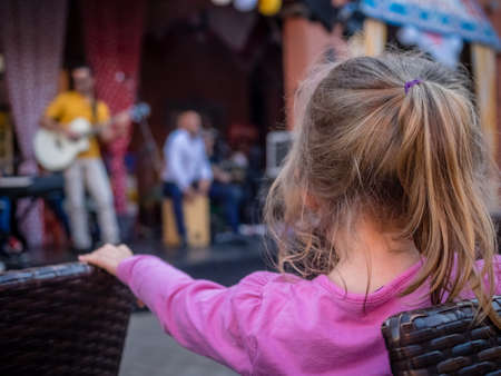 Four year old caucasian girl watching street band playing music during festival in Fuerteventura, Canary Islands, Spain