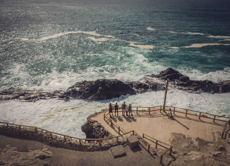 admiring: Group of tourists admiring the rocky coast in Ajuy, Parque Rural de Betancuria in Fuerteventura, Canary Island, Spain. Picture taken 13 April 2016