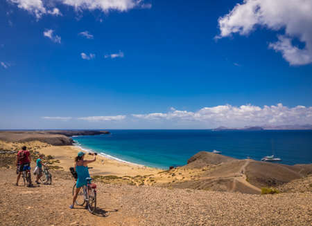 admiring: People on bicycles admiring the view of Playa Mujeres in Lanzarote, Canary Islands, Spain. Picture taken 20 April 2016.