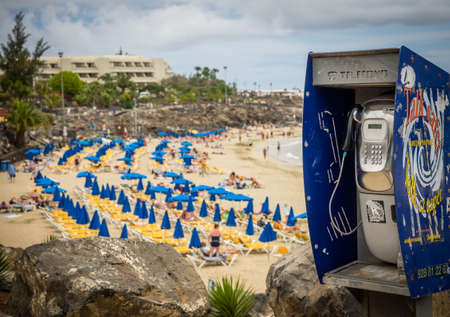 above 18: Public phone on the promenade above the puclic beach in Playa Blanca in Lanzarote, Canary Islands, Spain. Picture taken 18 April 2016