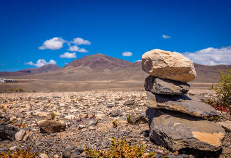 Pile of stones on the ground with the Pico de Redondo volcano and the landscape of southern Lanzarote in the background, Canary Islands, Spain Stock Photo