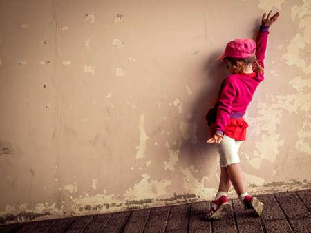 bailando salsa: Poco cuatro años de edad joven que practica sus movimientos de baile de salsa fuera de un edificio en ruinas