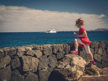 mujer mirando el horizonte: Poco cuatro años de edad joven de pie en el paseo marítimo y viendo la navegación de transbordadores de pasajeros de distancia en el mar Foto de archivo
