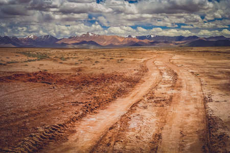 Muddy and clay mountain road through the high central Tibetan plateau, Tibet, China
