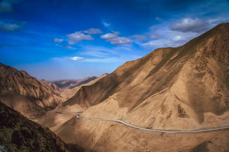 Twisting mountain road in Xinjang province in China leading to Western Tibet Stock Photo