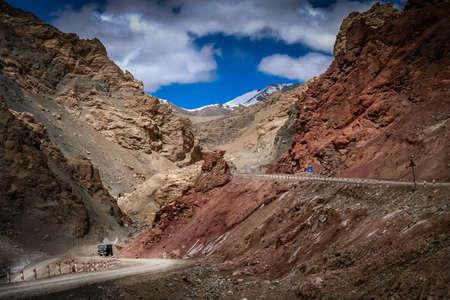 autobuses chinos que se mueve lentamente cuesta arriba en una carretera de montaña a través del oeste del Tíbet, China Foto de archivo