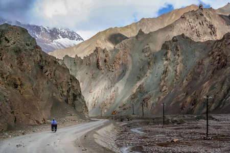 Solo female cyclist on the bicycle on the remote road in Western Tibet Stock Photo