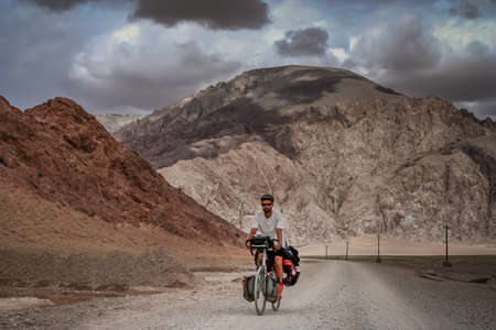 Solo male cycle touring through the stunning remote landscape of Western Tibet