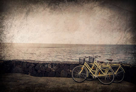 rested: Two old retro vintage bicycles rested on a stone wall on the seaside in Lanzarote, Canary Islands, Spain
