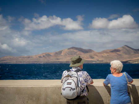 playa blanca: A senior couple looking out at the ocean at the harbour in Playa Blanca in Lanzarote, Canary Islands, Spain. Picture taken in April 2016 in Puerto del Carmen in Lanzarote, Spain