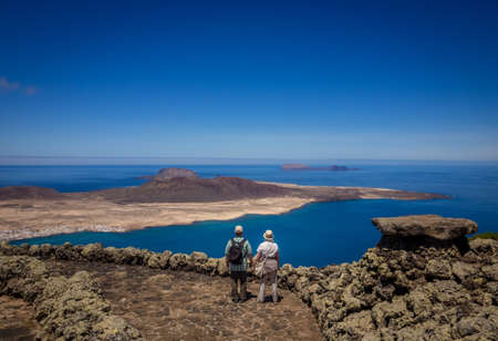 Lanzarote, Spain -  August 2016: Couple of seniors admiring the view of the La Graciosa, Allegranza and Montana Clara islands as seen from the viewing platform of  the Mirador del Rio, Lanzarote, Canary Islands, Spain Editorial