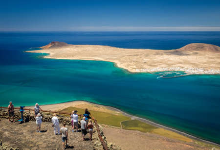 canarian: Lanzarote, Spain -  August 22, 2016:  Tourists admiring the view on the La Graciosa, Allegranza and Montana Clara islands as seen from the viewing platform of  the Mirador del Rio, Lanzarote, Canary Islands, Spain Editorial