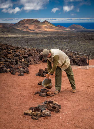 Lanzarote, Spain -  August 23, 2016: Man putting water into a steaming volcanic hole creating geyser, Timanfaya National Park, Lanzarote, Canary Islands, Spain Editorial