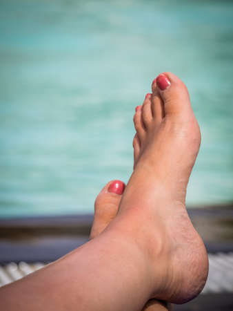 painted toenails: Closeup of feet of a woman sunbathing at deckchair by the swimming pool in a holiday resort