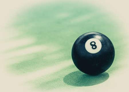 Black billard ball number eight on green billard table Stock Photo