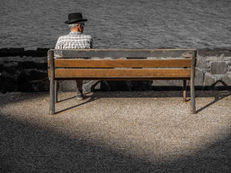 bench alone: Old lonely man sitting alone on a wooden bench on a seaside promenade in summer
