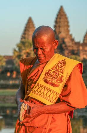 Angkor Wat, Cambodia -  August 2007: Monk praying in front of Angkor Wat, Cambodia