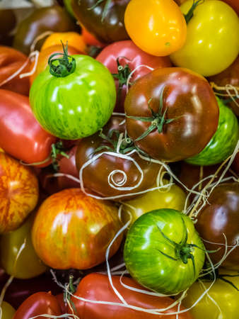 Fresh red, brown, yellow and green ripe tomatoes in wooden baskets on sale on a farmers Borough Market in London Stock Photo