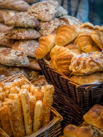 gressins: Close up of freshly baked buns, croissants and breadsticks on market stall in Borough market in London