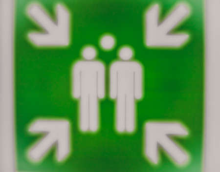 assembly point: Soft focus green sign indicating the assembly point for people in case of fire Stock Photo