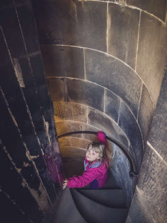 scott monument: Little girl going down the narrow spiral stairs inside the Walter Scott monument in Princes Street, Edinburgh, Scotland Stock Photo