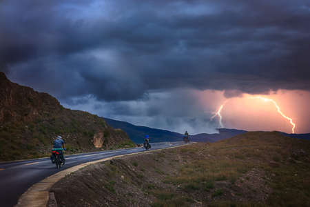 Three travellers on bicycles cycling on a road in asia during stormy weather Stock Photo