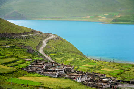 Traditional tibetan homes on the slope of the hill on the shore of the stunning Yamdrok Tso Lake lake in Central Tibet, China. Stock Photo
