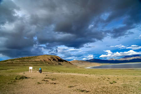 Solo female cyclist on the bicycle in the stunning remote part of Central Tibet Stock Photo