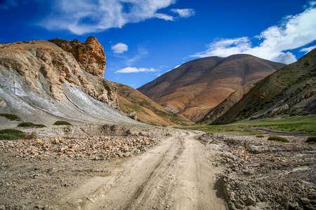 Dirt gravel mountain road through the high central Tibetan plateau, Tibet, China