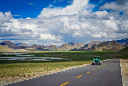 four peaks wilderness: Car driving on the paved mountain road from Ali to Lhasa through the high central Tibetan plateau, Tibet, China
