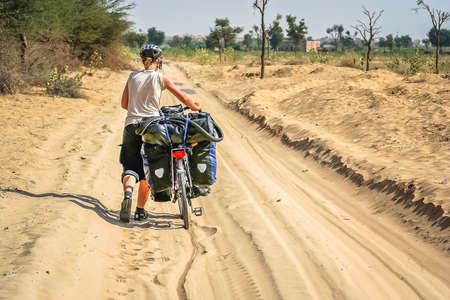 touring: Woman pushing her bicycle through the sand while cycling through remote desert road in Rajasthan, India