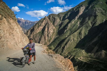 Single male cyclist pushing the bicycle on the remote, difficult to ride on rocky road in Eastern Tibet