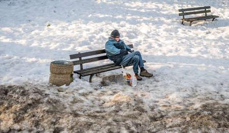 marginalized: Szklarska Poreba, Poland -  February 2017 :  A homeless man resting on a bench in a park in winter, Szklarska Poreba, Poland