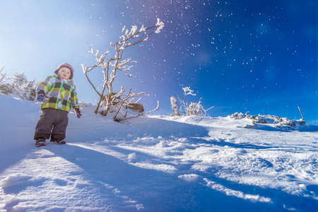 Portrait of a little boy standing in the snow on the top of a mountain in winter