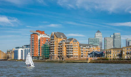 executive apartment: London, England -  25 March 2017 : Sailboat on the river Thames with the riverside apartments in the background, London, UK Editorial