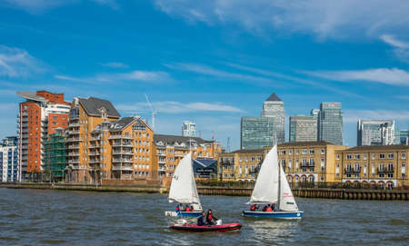 London, England -  25 March 2017 : Sailboats on the river Thames with the Canary Wharf commercial buildingsin the background, London, UK Editorial