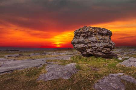 Huge limestone glacial erratic boulder on the cliffs in Doolins Bay, The Burren, County Clare, Ireland