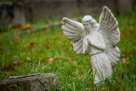 Tiny angel figure next to a grave in cemetery