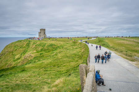 sightseers: Cliffs of Moher, Ireland -  April 2017 : Tourists walking on a pathway leading to the O Briens Tower at the Cliffs of Moher, Ireland