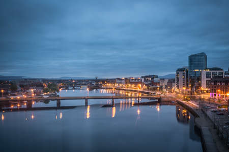 Limerick, Ireland -  April 2017 : View of the bridges over river Shannon, hotels and commercial buildings in Limerick town after sunset, Ireland Editorial