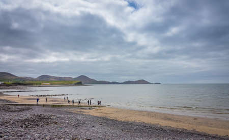 chaplin: Waterville, Ireland -  April 2017 : Group of tourists walking on the Ballingskelligs Bay Beach, Waterville, County Kerry, Ireland